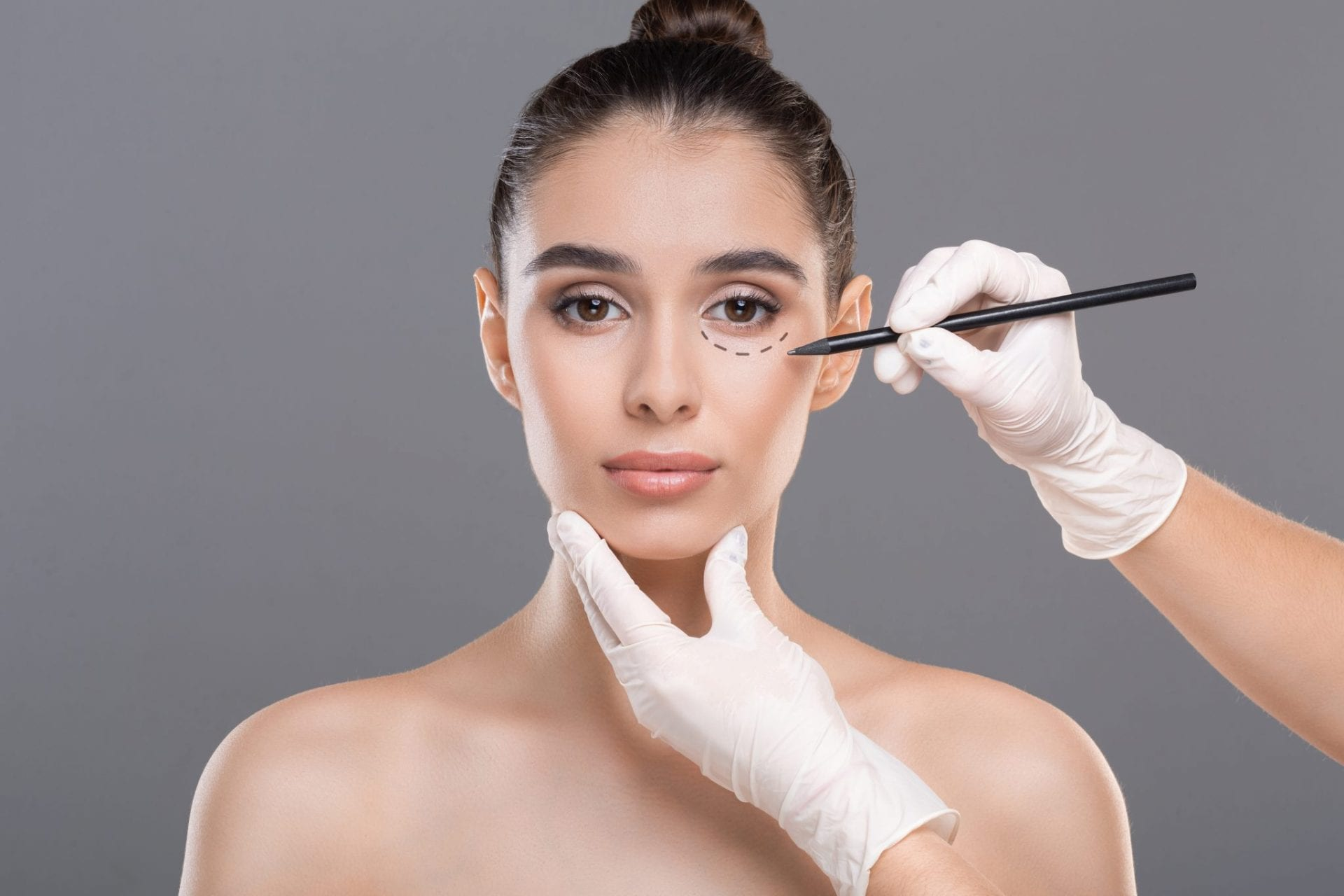 Doctor drawing marks on female face before procedure